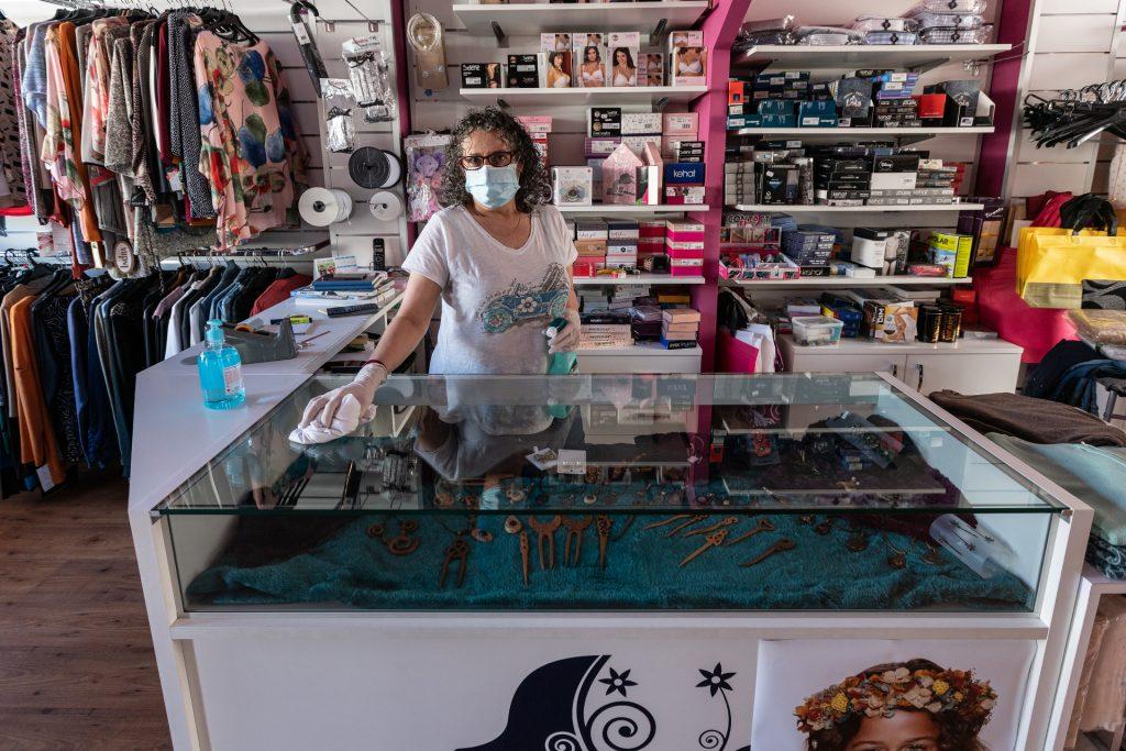 Marité Vieira desinfectando o mostrador do seu negocio despois de atender unha persoa